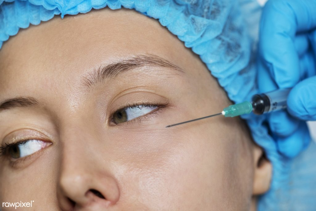 Female patient in blue hair cap looks to her right as needle is injected into her lower eye for the non-surgical facelift