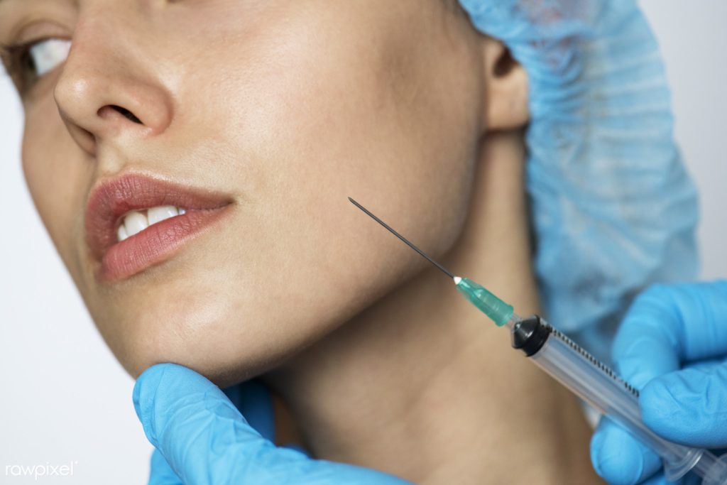 White female patient with blue hair cap on holds still as a needle is held up to her face for the non-surgical face lift.