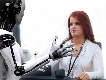 Woman in white coat sits at desk opposite a prototype AI robot that has the physical structure similar to a human
