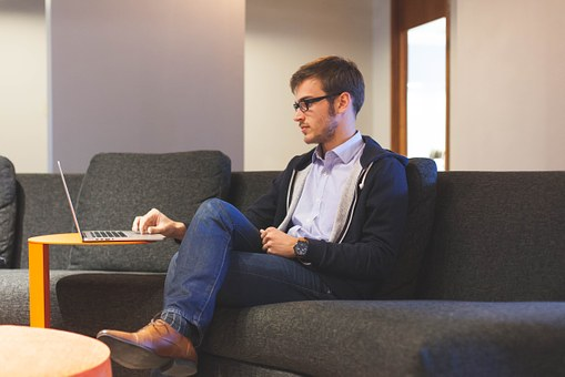 Man sits cross-legged on a sofa looking at his start-up plans on his laptop